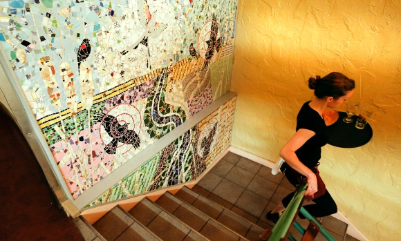 Free State server Elizabeth Cunningham makes her way down the stairs past a wall mosaic created by Lawrence artist Lora Jost. Nick Krug/Journal-World Photo